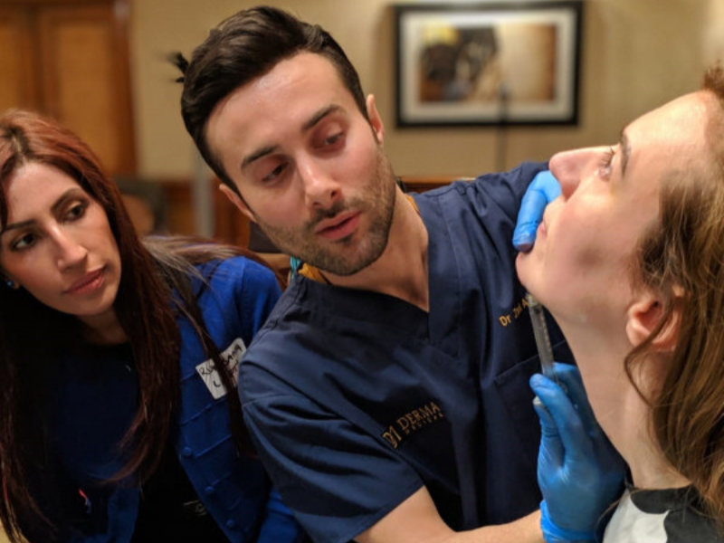 Dr Zack Ally injecting someones chin with dermal filler
