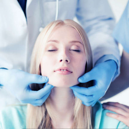 A lady having her jaw examined by a doctor wearing gloves